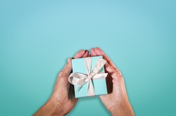 hands holding a turquoise gift boxe tied with white silk ribbon. Suitable for concepts like luxury gift, anniversary, Valentine's day, Mother's day or christmas. Copy space available