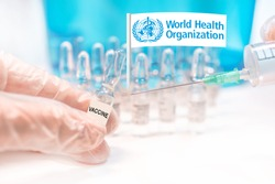 Hands holding a vaccine vial and a syringe, rows of capsules and a flag of WHO (World Health Organization), illustrating COVAX Facilities' plans for global vaccination against Covid-19 (SARS-CoV-2).