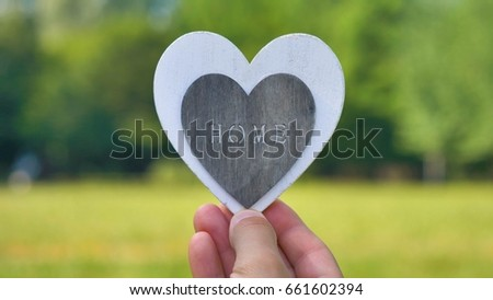 """Hands holding a white gray wooden silhouette in the form of a heart, the inscription """"Home"""", a background of nature. Concept: a sweet house, to love a family, hands in the shape of a heart, blue. #661602394"""