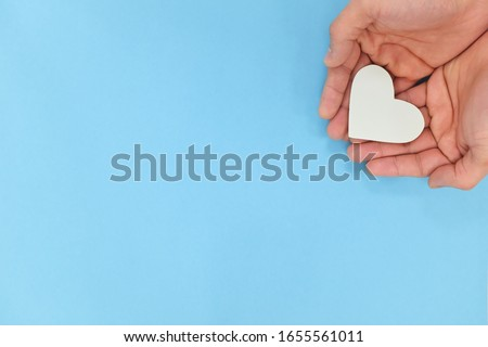 Hands holding a white heart in blue background with copy space. Kindness, charity, pure love and compassion concept.
