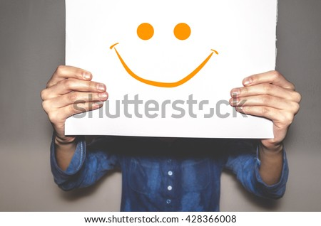 Shutterstock Hands holding a withe cartel with a smiley face.