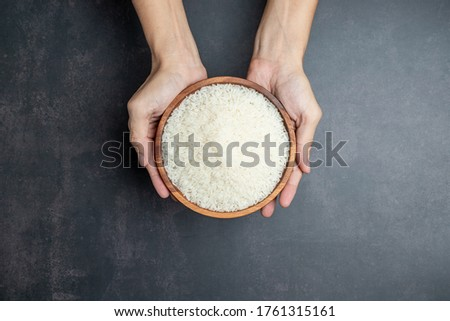 Hands holding a wooden bowl of rice grains for zakat, Islamic zakat concept. Muslims to help the poor and needy. Conceptual shoot for property, income, and fitrah zakat. Stock photo ©