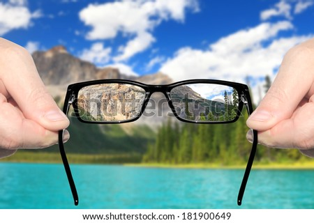 Hands holding and offering eye glasses to look at amazing mountain lake landscape.Sharp as a good sight symbol and unsharp as a bad sight symbol