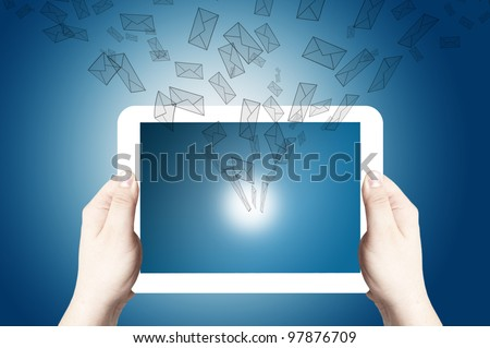 Hands holding and point on white digital tablet with 3D mail icon coming from the screen on blue background - stock photo