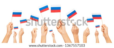 Hands holding and raising small flags of Russia #1367557103
