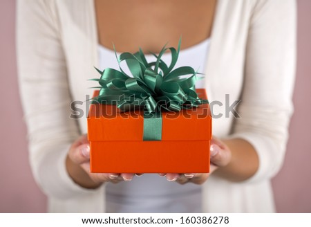 Hands holding beautiful gift box, female giving gift, Christmas holidays and greeting season concept, shallow dof