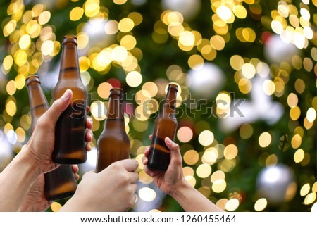 Hands holding beer bottles and happy enjoying harvest time together to clinking glasses at outdoor party on beautiful bokeh night light background.Celebration drinking beer in pub orbar.          #1260455464