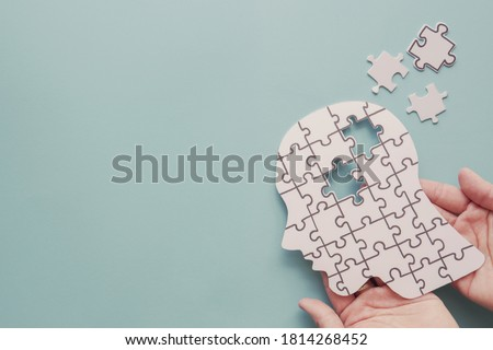 Hands holding brain with puzzle paper cutout, autism, memory loss, dementia and alzheimer awareness, world mental health day concept