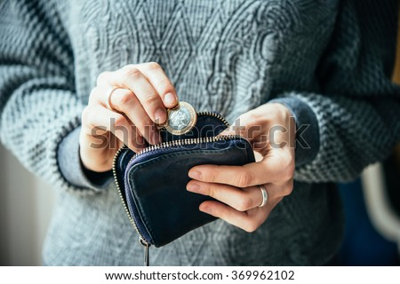 Hands holding british pound coin and small money pouch