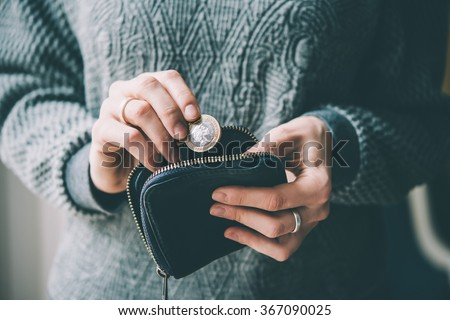 Hands holding british pound coin and small money pouch. Toned picture