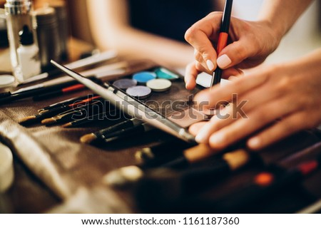 hands holding brush and eyeshadow palette. makeup artist making gorgeous make-up for bride in the morning. beauty and fashion image. set of brushes, powder, eyeshadows on table