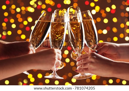 Hands holding champagne glasses on lights background #781074205
