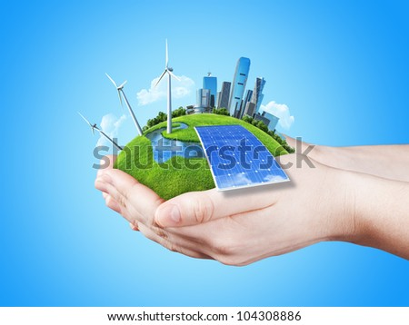 Hands holding clear green meadow with sun battery block, wind mill turbines and city skyscrapers. Concept for ecology, growing business, freshness, freedom. Green fields collection.