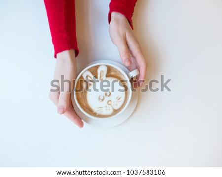 Hands holding coffee. Top view of hot coffee latte art bunny foam on white background. A cup of bunny latte art coffee. Close up of beautiful female hands holding big white cup of cappuccino coffee.