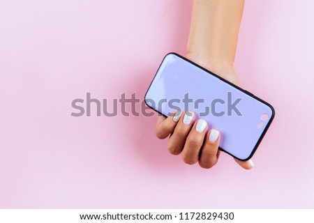 hands holding colorful smartphone case. Pink Background