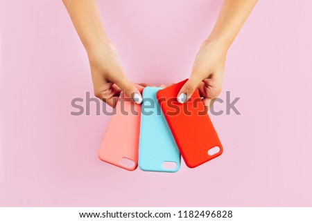 Photo of  hands holding colorful smartphone cases. Pink Background
