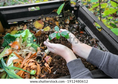 hands holding compost above the composter with organic waste