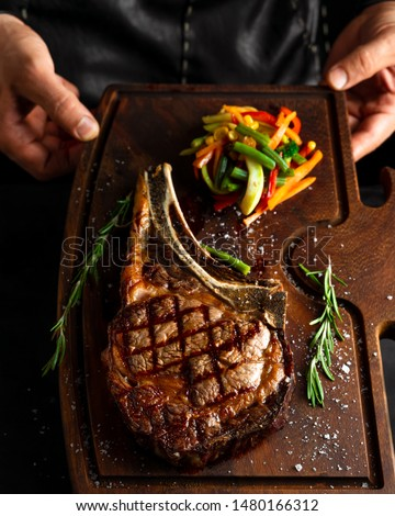 Hands holding cooked Tomahawk (long bone ribeye) steak on a serving board. Low key image, vertical orientation