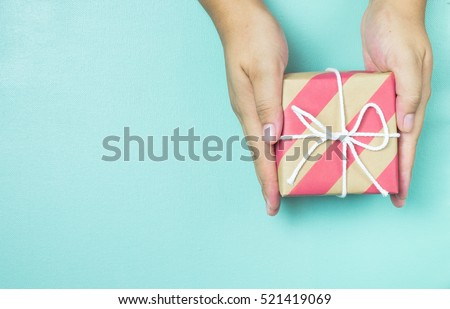 Hands holding craft paper gift box with as a present for Christmas, new year, valentine day or anniversary on blue background, top view