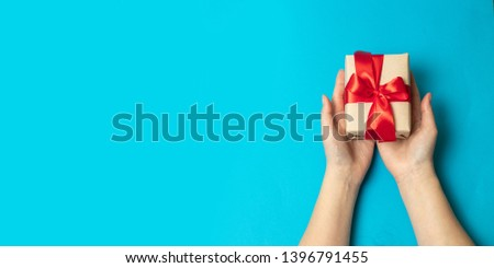 Hands holding craft paper wrapped present box in package with red ribbon