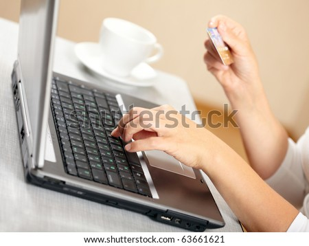 Hands holding credit card and laptop. Shallow DOF