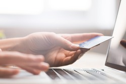 Hands holding credit card, typing on the keyboard of laptop, onine shopping detail close up
