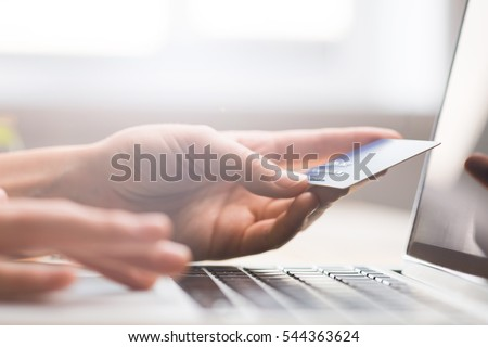 Hands holding credit card, typing on the keyboard of laptop, onine shopping detail close up #544363624