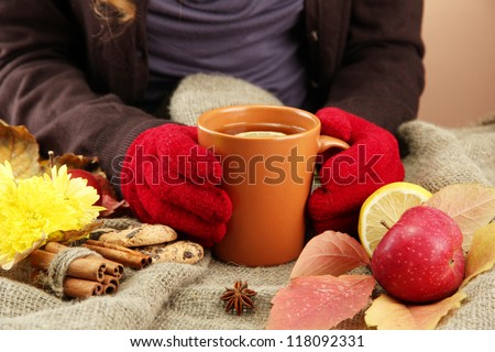 hands holding cup of hot drink and autumn leaves, on burlap background