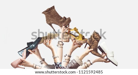 Hands holding different shoes on isolated background #1121592485