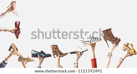 Hands holding different shoes on isolated background #1121592491
