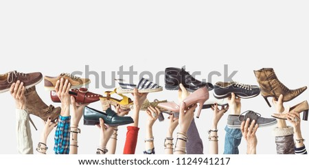 Hands holding different shoes on isolated background - Shutterstock ID 1124941217
