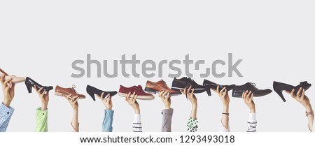 Hands holding different shoes on isolated background #1293493018