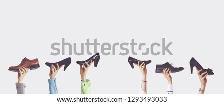 Hands holding different shoes on isolated background #1293493033