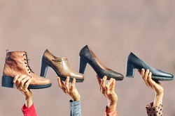 Hands holding different women shoes and boots. Concept of selection, purchase and repair of shoes
