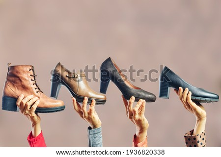 Hands holding different women shoes and boots. Concept of selection, purchase and repair of shoes ストックフォト ©