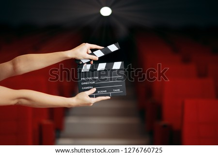 Hands Holding Director Movie Clapper in Cinema Theater. Film slate announcing premiere in movie theatre