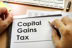 Hands holding documents with title capital gains tax CGT.
