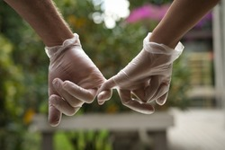 Hands holding each other with the little finger wearing sanitary gloves. Close up. COVID-19 concept