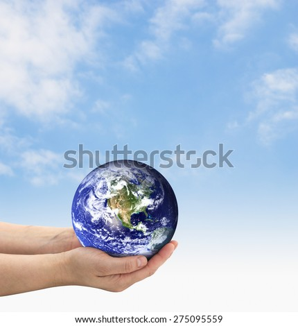 Hands holding earth on a blue sky. The planet earth image provided by NASA.