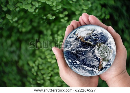 Hands holding earth on green swirly bokeh. Elements of this image furnished by NASA