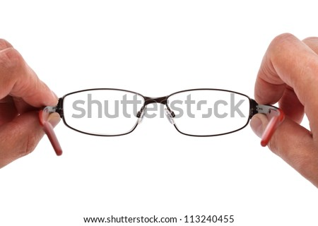 Hands holding eye glasses in front of white background