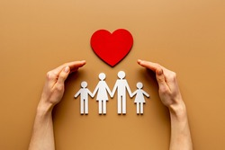 Hands holding family figure. Life and health insurance concept.