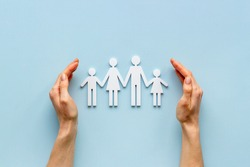 Hands holding family figure top view. Insurance concept