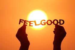 Hands holding Feel good paper cut text over sunrise orange sky