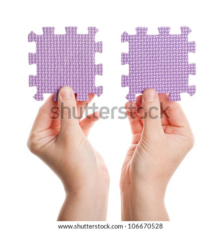 Hands holding foam puzzle pieces isolated on white