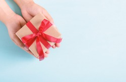 Hands holding gift box with red ribbon for giving on pastel background