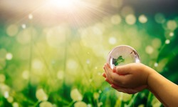 Hands  holding glass green planet on sunny background. Save Earth. Concept of the Environment World Earth Day Banner.