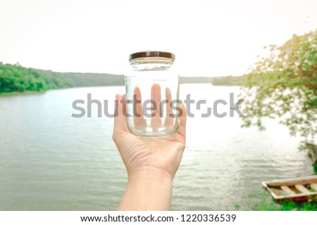 Hands holding glass jar for keeping fresh air, concept of clean atmosphere, fresh air and a green environment.