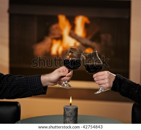 Hands holding glass of red wine, clinking in front of fireplace.