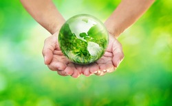 Hands holding globe glass earth with green grass field in side on blurred light nature background,  World Environment Day and Creating the Green Clean World with Your Own Way Concept